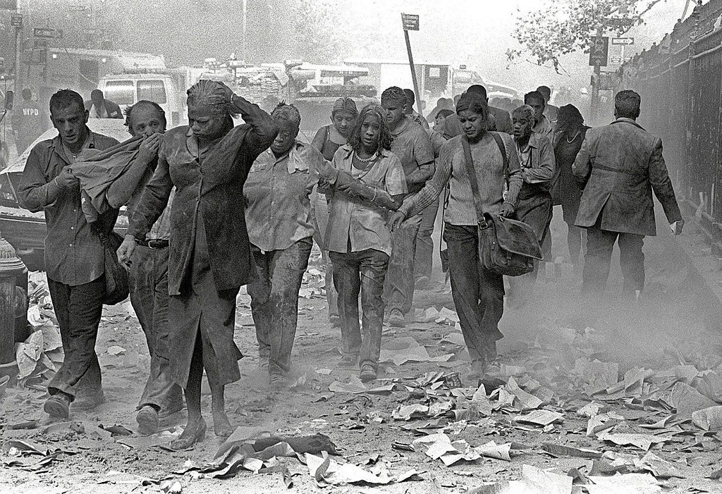 FILE - In this Sept. 11, 2001 file photo, people covered in dust walk over debris near the World Trade Center in New York. (AP Photo/Gulnara Samoilova)