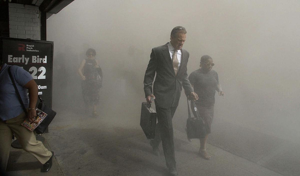 FILE - In this Tuesday, Sept. 11, 2001 file photo, pedestrians flee the dust-filled area surrounding the World Trade Center following a terrorist attack on the New York landmark. (AP Photo/Amy Sancetta)