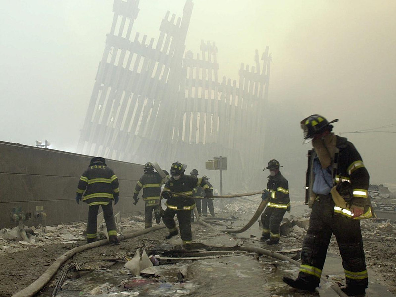 FILE - In this Tuesday, Sept. 11, 2001 file photo, with the skeleton of the World Trade Center twin towers in the background, New York City firefighters work amid debris on Cortlandt St. after the terrorist attacks. (AP Photo/Mark Lennihan)