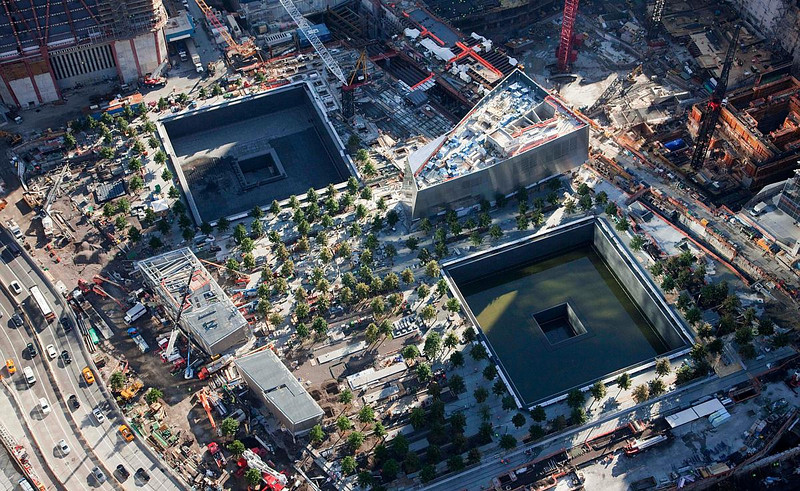 In this aerial photo of July 28, 2011, a grove of trees surround massive square reflecting pools at the National September 11 Memorial in New York. The memorial will open to the public on Sept. 12, 2011. Out of the ashes of 9/11 has risen a vibrant neighborhood packed with new restaurants and hotels, places to live and spots to shop, along with many ways to pay respects to an area some worried would never come back.