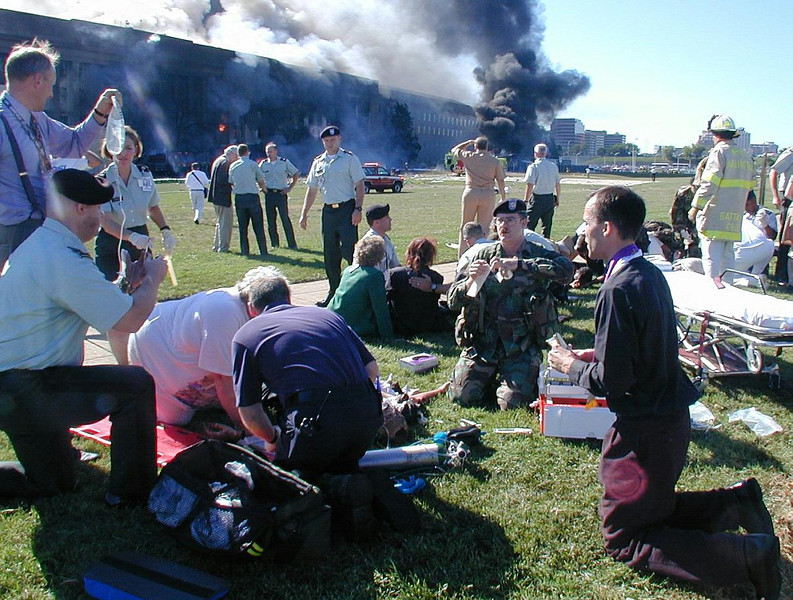 FILE - In this Tuesday, Sept. 11, 2001 file photo, a priest prays over a wounded man outside the west entrance of the Pentagon as emergency workers from all services help the wounded after a terrorist attack on the Department of Defense building in Washington. (AP Photo/Navy Times, Mark Faram)