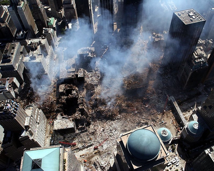 Building 7's 3-storey high neat debris pile, can be seen off to the left. <br /> WTC 5 &amp; 6 stood between the North Tower &amp; Building 7, yet remained standing.  Aluminum oxide (a by-product of the thermitic reaction, seen as white smoke) poured from all three sites for months afterwards.