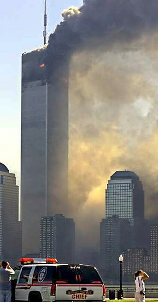 "<span style=""font-size: small;""><span style=""font-family: arial;"">The North Tower stood alone for almost 30 minutes, before being destroyed. This photo is important because it gives a good idea of just how much of it remained intact below the point of impact. These buildings were designed specifically with airliner impacts in mind.    <br><br>In their day, the Twin Towers were the tallest buildings ever constructed.  The revolutionary, award-winning, 'tube-in-tube' design they first made use of remains the standard used in steel hi-rise construction to this day.  Because of their unique, tightly full cross-braced outer column assembly arrangement, they were among most strongest (in terms of redundancy ratio) buildings ever constructed.  </span></span>"