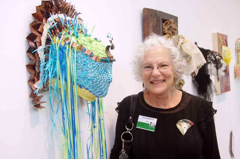 Artist Carol Binstock stands with her colorful fine art mask.