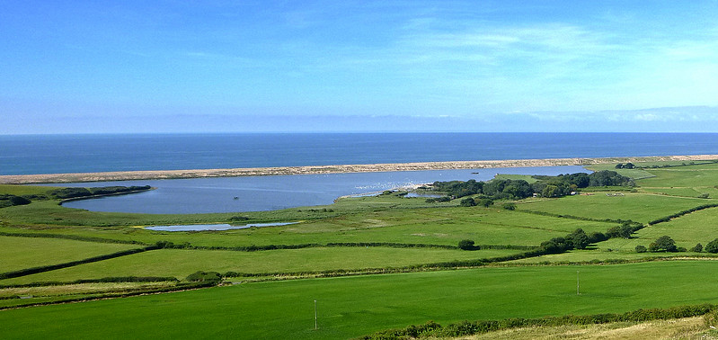 An early view across the Fleet and Chesil Beach.   The white smudge just right of centre is the population of wild swans congregating at the Swannery.