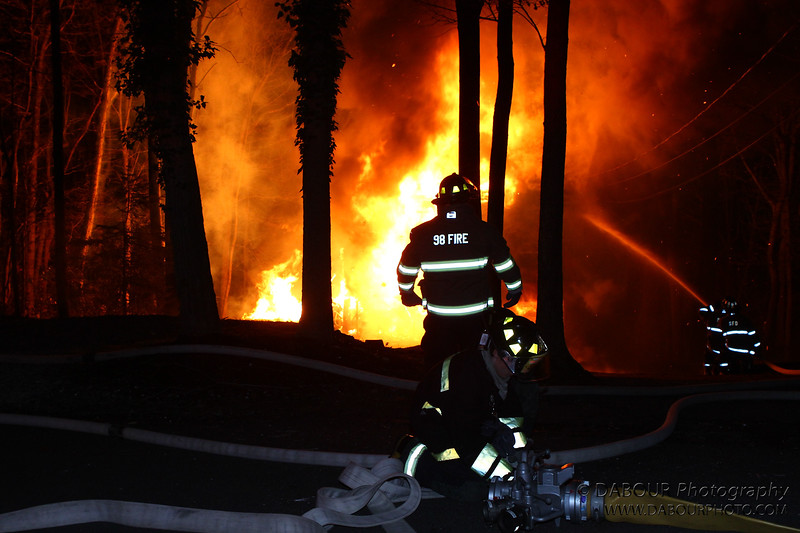 Members of the Stewartsville Vol. Fire Company start attacking the house fire with tanker water