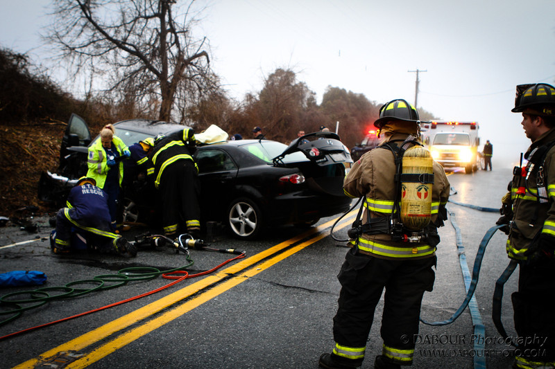 Members of the Stewartsville Vol. Fire Company stand ready as members of the rescue squad treat one of the drivers involved in the two vehicle collission on SR 173 in Greenwich Twp  NJ Saturday morning. Express-Times Photo | DAVE DABOUR