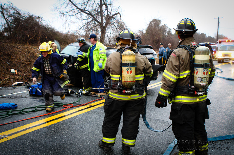 Members of the Stewartsville Vol. Fire Company stand ready as members of the rescue squad treat one of the drivers involved in the two vehicle collission on SR 173 in Greenwich Twp NJ. Express-Times Photo | DAVE DABOUR