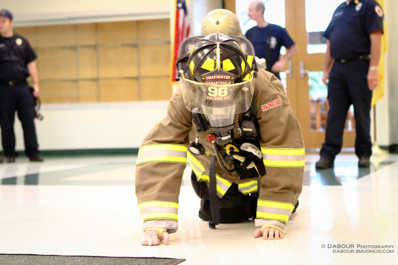 Firefighter Cody shows students how a firefighter might greet you during a fire