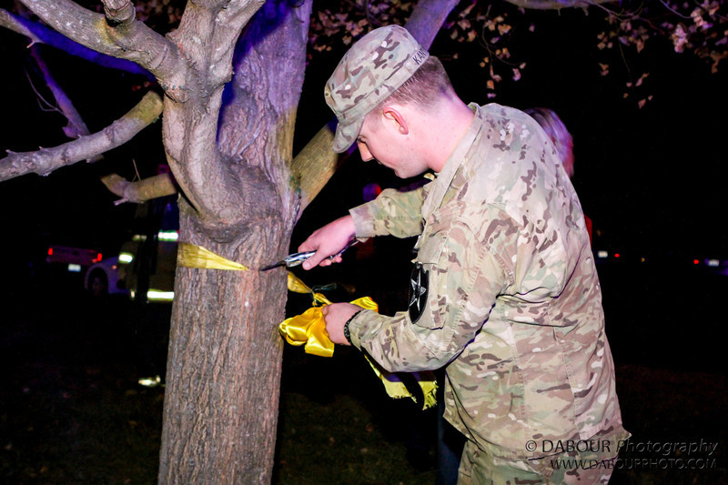 Ryan takes down the yellow ribbon on the tree outside his home as he is home forr the holiday season
