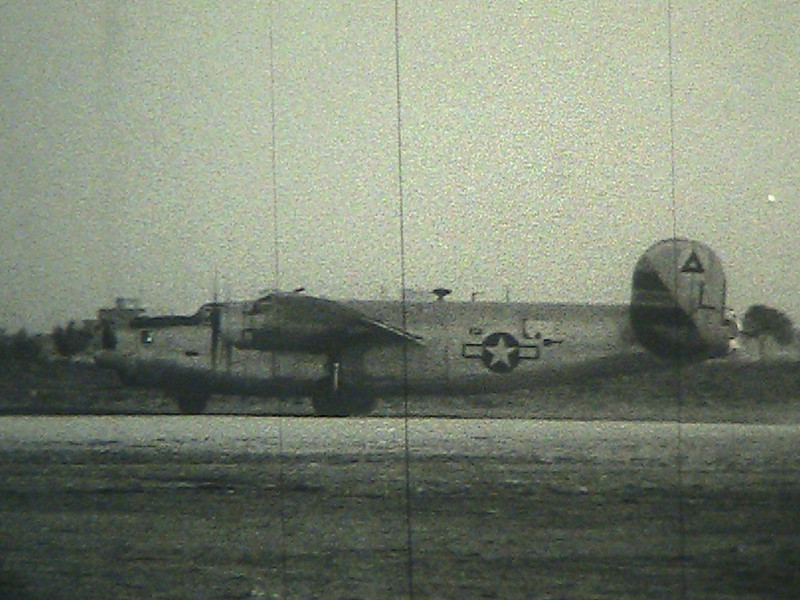"Still shot taken from the film -- I believe this is my grandfather's aircraft, 526-L.. There are no oter ""L"" aircraft flying that day -- Aircraft 258-I (with the girl on the nose art, coming up) has a smaller L on the tail but is clearly otherwise identified."