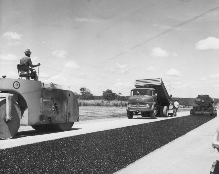 Asfaltando as estradas da Lunda, aplicando uma pequena camada de alcatrão com máquinas de baixo rendimento.