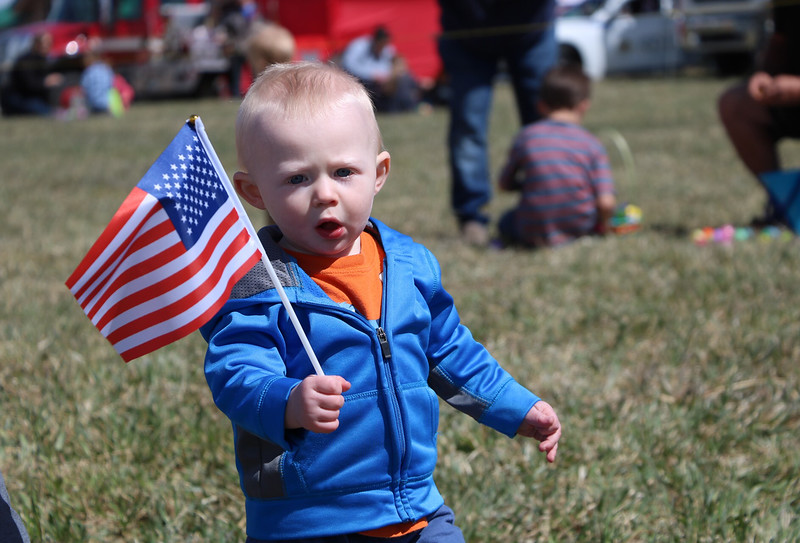"Liam Flaherty, 1, waves a flag during the Easter egg hunt at ""A. Day of Kindness"" in Berthoud on Saturday."