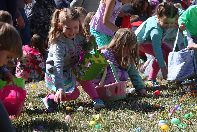 "Kindergarteners and first graders race to pick up plastic Easter eggs filled with candy at ""A. Day of Kindness"" in Berthoud on Saturday. Volunteers spent weeks leading up to the fair filling each egg with a prize, event organizer Julia Sabados said."