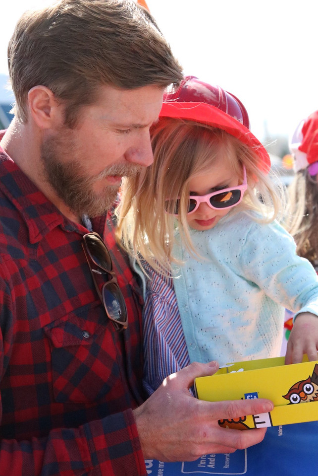 "Joe Cartlidge holds his daughter Olive, 3, as they look at free pairs of children's shoes offered to families in need at ""A. Day of Kindness"" in Berthoud on Saturday, March 31, 2018."