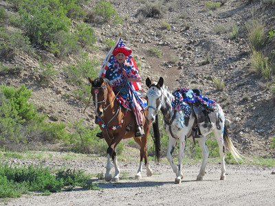 Our Owyhee Parade Mistress, Linda, aboard Ted and leading Hattie in our Owyhee, Idaho Fourth of July celebration