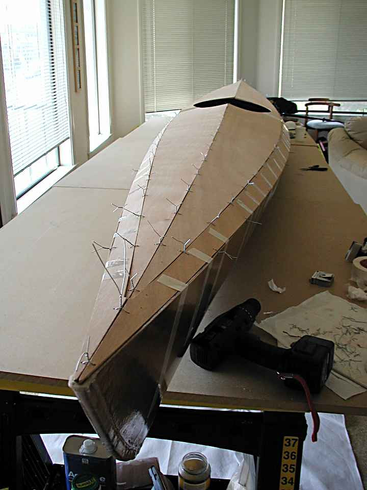 "Everything may look ok but there's a slight ""bulge"" in the hull  back aft on the port side; the deck just doesn't want to lie flush with it.  I added a few extra twists to force it to line up so the cured epoxy would hold it fast. Then the deck and keel seams are filled with epoxy and left to cure for a few days."