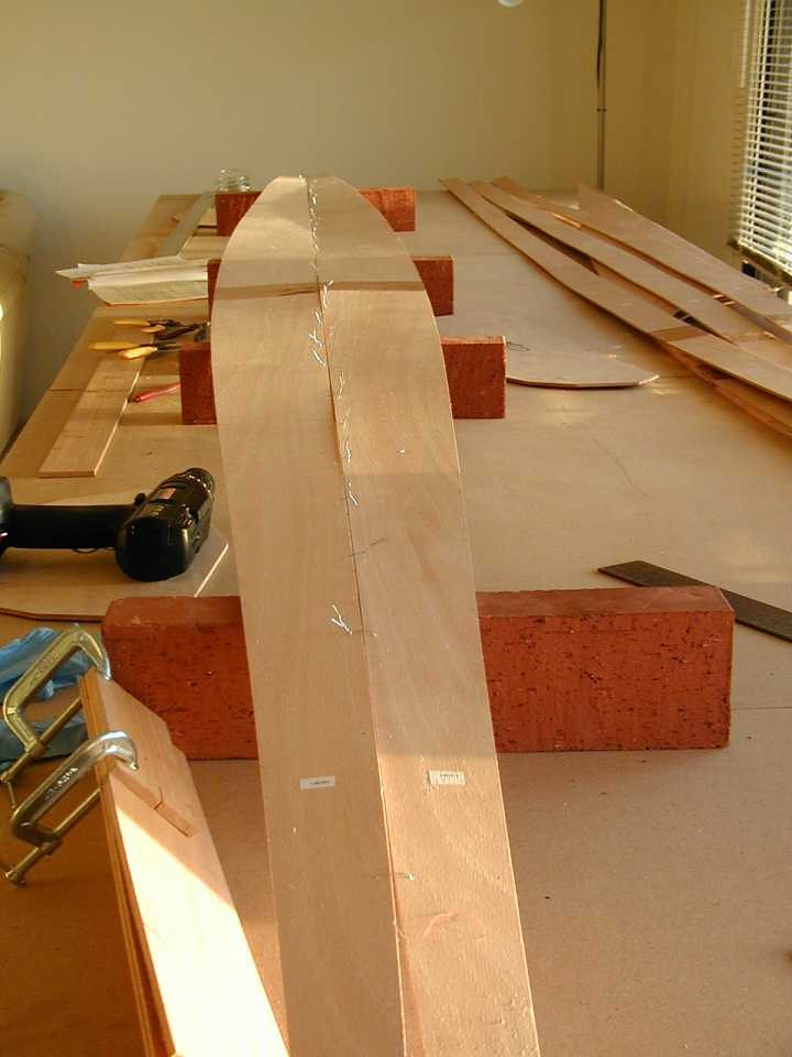Once the 2-piece keel planks are epoxyed together, it's time to stitch them together by drilling holes and inserting wires. Twisting these wires together will bend the planks into the correct shape (hopefully).