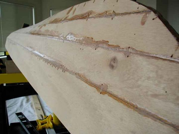 Once the epoxy has set, the stitches are removed and --- voila! --- you have a mahogany hull with dozens of tiny holes in it.  And the excess epoxy along the seams has to be sanded as flat as possible, otherwise this next step will be fraught with problems...