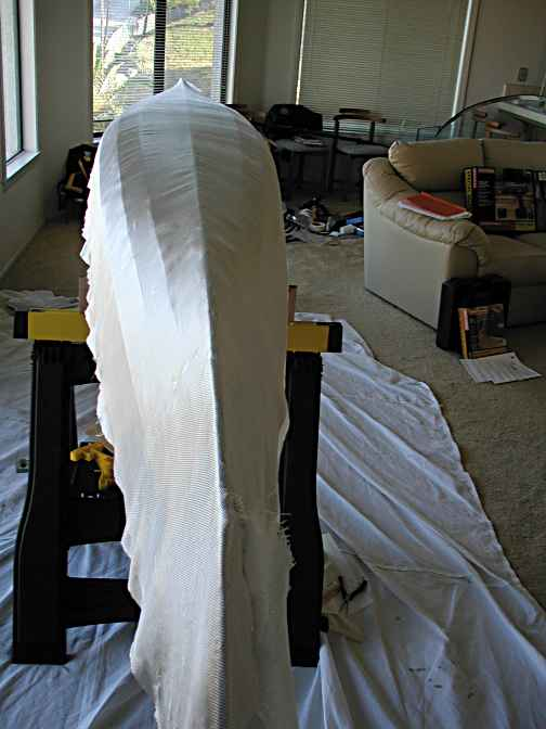 First a saturation coat of epoxy is rolled on with a paint roller, then the fiberglass cloth is draped over the hull.  To conform to the hull's shape you must trim and overlap the cloth. This becomes tricky on the bow and stern.