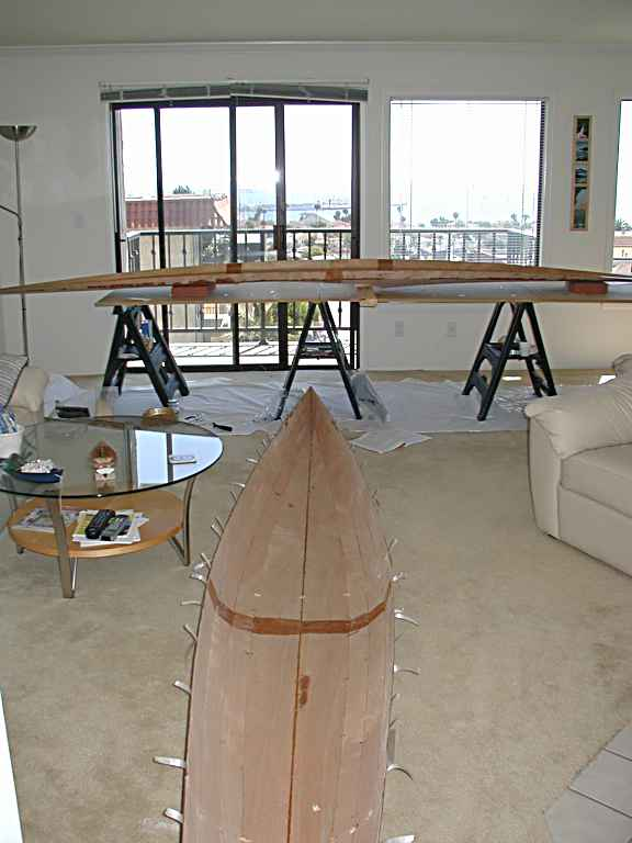 Let's not forget the deck planks...These are also stitched together and an epoxy saturation coat rolled on both sides.  The deck is on the work table and the tape on the hull is for experimentation of the fit of the deck on the hull.