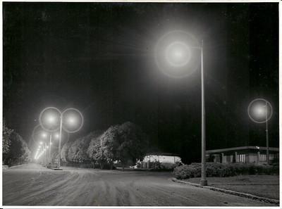 """Avenida do Obelisco, casa em frente ao Museu Inauguração da iluminação pública, que veio substituir o """"prato"""" com uma lampada que geralmente havia em cada cruzamento. As ruas ainda não estavam alcatroadas."""