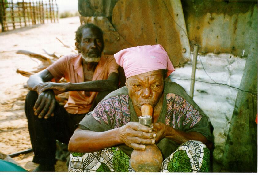 Mae camponesa fumando mutopa na aldeia Samulambo Camissombo 1999