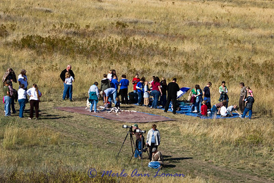 A learning area for school children. Bones and other learning tools are at the site and an interpreter provides information.  Visitors are set up to photograph the bison.