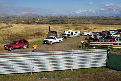 Looking back at the parking area. On the right, just out of the photo, is a corral with horses that are used for some of the work. A volunteer, in an orange vest, directs traffic.