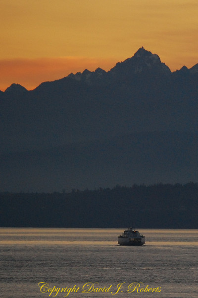 A ferry plies the waters between Port Townsend and Keystone on Whidbey Island in the early evening light. Olympic Mountains in the distance.