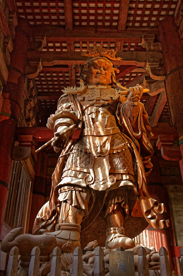 Komokuten, one of Four Heavenly Guardian Kings and one of two guardian figures that stand to either side behind the Great Buddha. He is also a calligrapher, holding a lettering brush in his right hand and a scroll in his left.