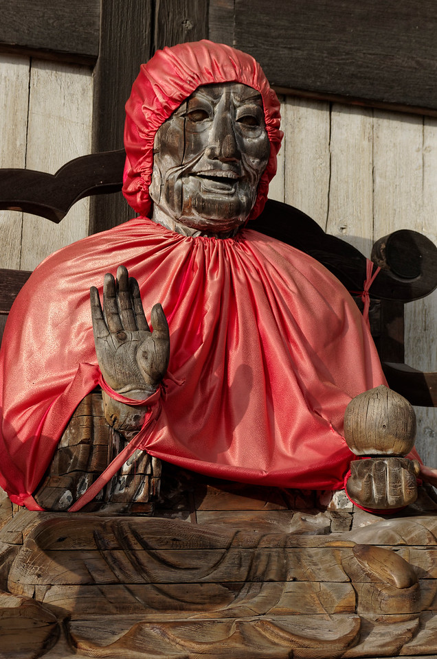 Just outside the Great Buddha Hall, this seated wooden figure with crystal eyes is Binzuru (St. Pindola in Sanskrit), who was the leader of Buddha's 16 disciples. Though he achieved the highest sainthood, spreading and sharing Buddha's teachings, his display of self-importance before the people led the Buddha to order him to remain seated outside the temple. A common belief is that rubbing a part of his body will cure any pain or illness in the corresponding part of one's own body. His cap and bib were given by people whose sicknesses were cured. Paint originally covering him has all but disappeared over the years.