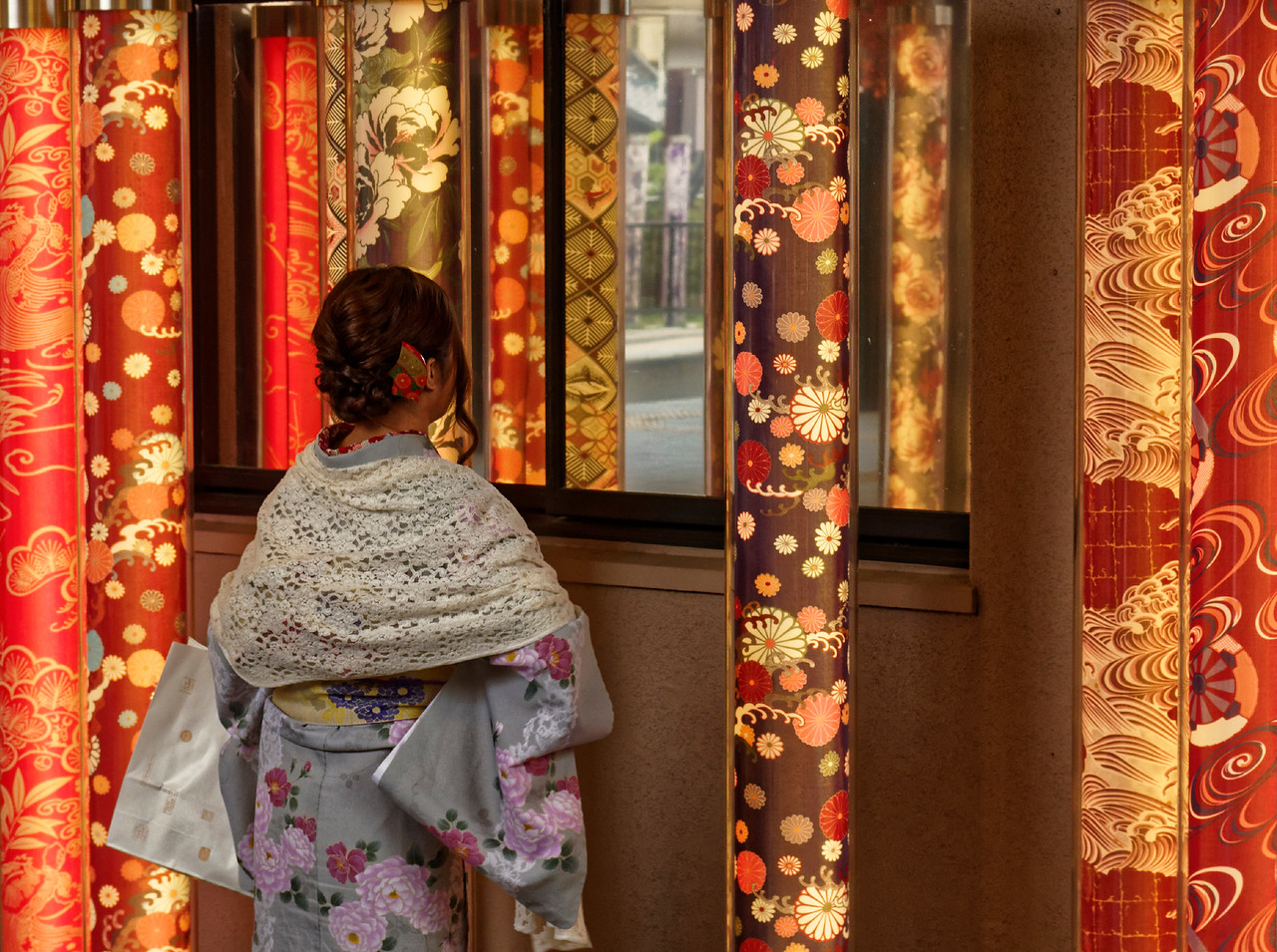 At the train station at Arashiyama, western Kyoto, kimono fabrics have been placed within tall, illuminated tubes, making for a very colorful display.