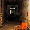 Red chair in the hallway of abandoned Forest Haven Asylum - a color image