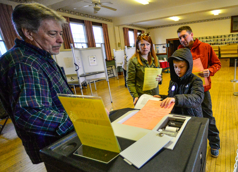 Camren Saunders, 9, of Rockingham, Vt., puts a local election ballot into the tabulator at the Masonic Temple, in Bellows Falls, Vt., on Super Tuesday on March 3, 2020. Kristopher Radder, Brattleboro Reformer via AP