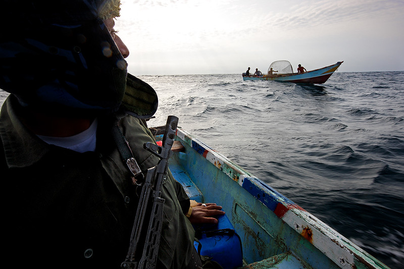 Soldier in boat with fishermen.