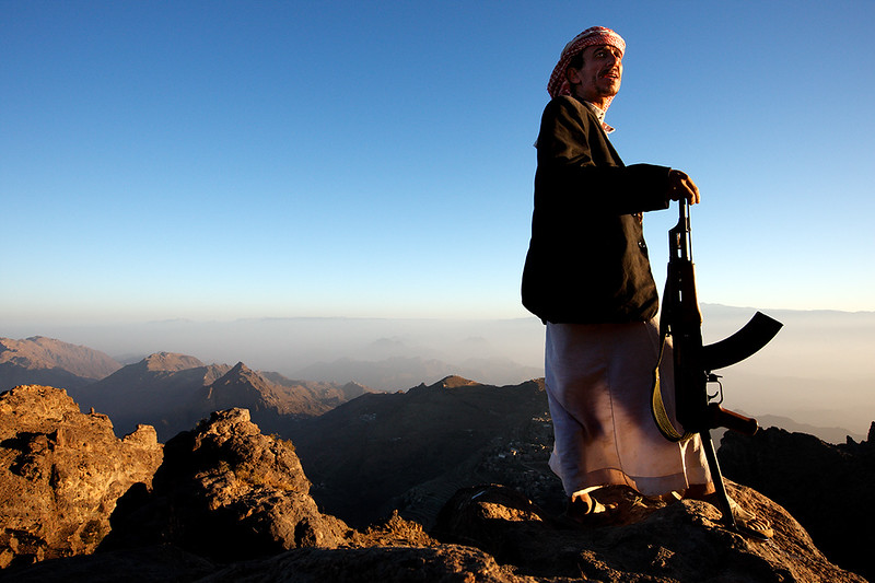 Man from al-Hijan looking around the mountains while carrying his machine gun.
