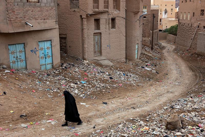 Woman walking among houses in Tarim.