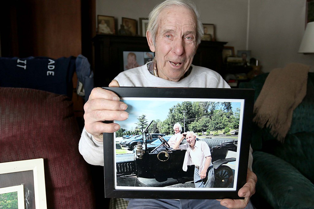 . Harvey Price holds a picture of him and his wife Agnes Price with his 1915 Model-T. Harvey talked about his wife, who just passed away, at his home in Lunenburg on Friday morning. SENTINEL & ENTERPRISE/JOHN LOVE