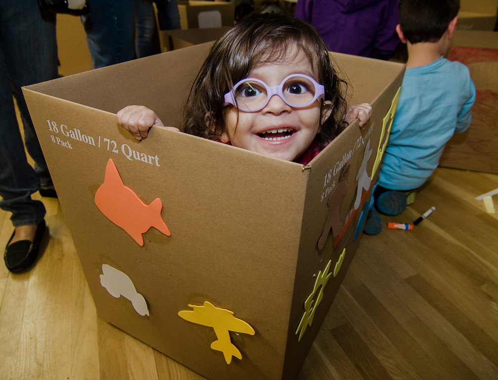 . Eliana Lara pops out of her cardboard car during the drive-in movie at Leominster City Hall on Thursday, February 23, 2017. Children were able to come in and design their own box car and enjoy pizza and snacks while watching \'Zootopia\' on a large projector screen. SENTINEL & ENTERPRISE / Ashley Green