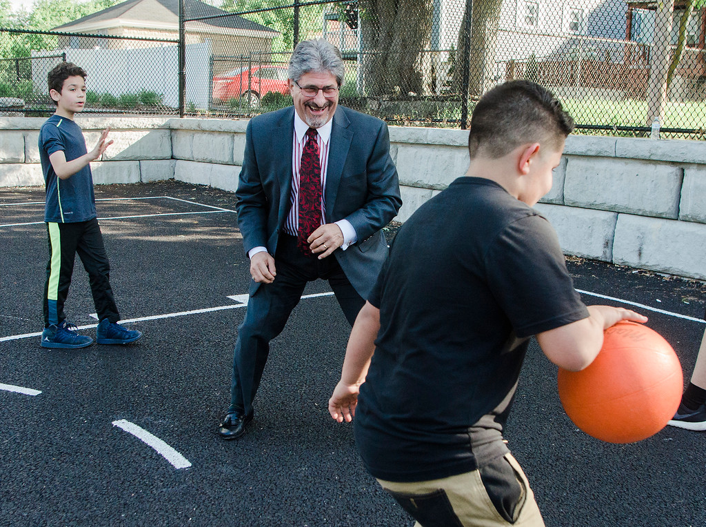. Mayor Stephen DiNatale shoots some hoops with Michael Cruz (foreground) and Aidyn Davis (background) during the ribbon cutting ceremony dedicating the rennovation of the park at First and Railroad Streets in Fitchburg on Wednesday, May 24, 2017. The once abandoned site is now home to a full court basketball court,  picnic area, benches, native plantings, and educational signage. The park features rain gardens and permeable pavement which filter storm water runoff, helping to protect the nearby Nashua River. SENTINEL & ENTERPRISE / Ashley Green