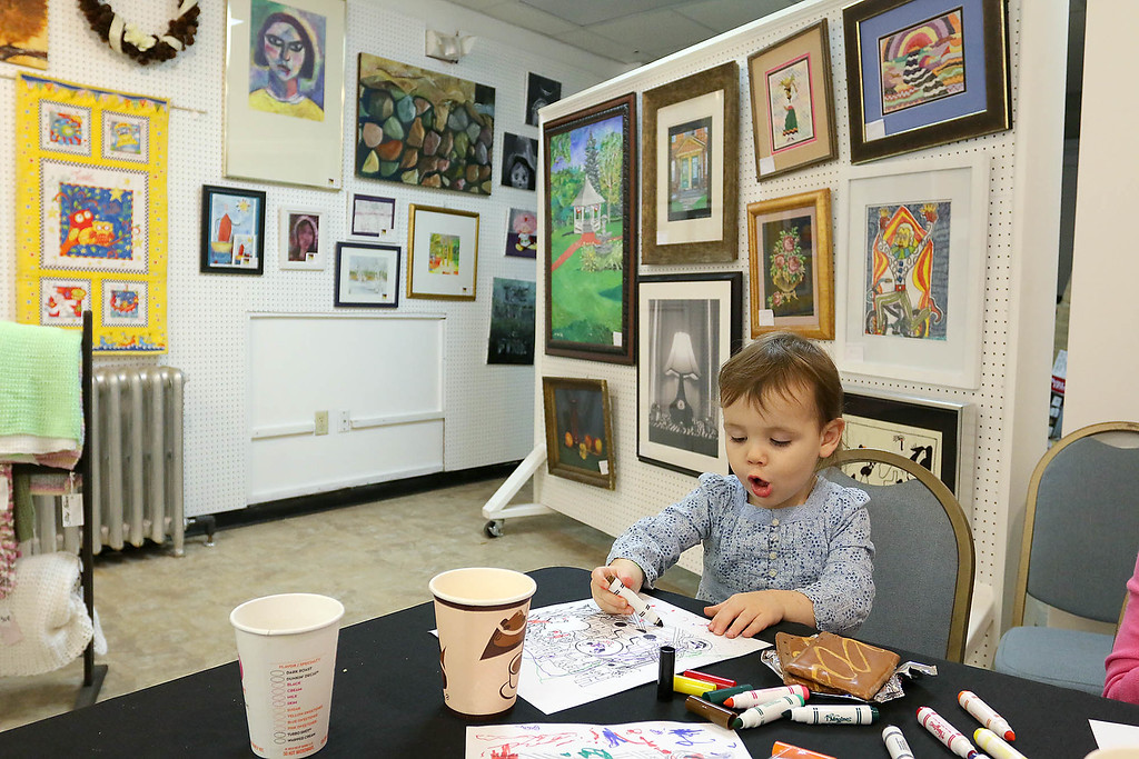 ". Surrounded by local artwork is Scarlet Horgan, 2, as she creates her own artwork after the ribbon cutting for the new ""The First Chapter\"" bookseller at MAKE on Main Street in Leominster Thursday morning.  SENTINEL & ENTERPRISE/JOHN LOVE"