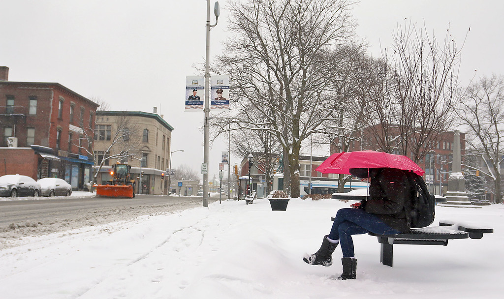 . Fitchburg resident Melissa (no last name given) tries to stay dry as she waits for the bus on Monument Square in Leominster. SENTINEL & ENTERPRISE/JOHN LOVE
