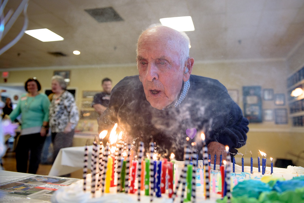 . Leominster native Malcom Brown takes a deep breath and swiftly blows out 100 candles at his 100th birthday celebration at the Veterans Memorial Center in Leominster on Sunday April 9, 2017.  (Sentinel & Enterprise photo/Jeff Porter)