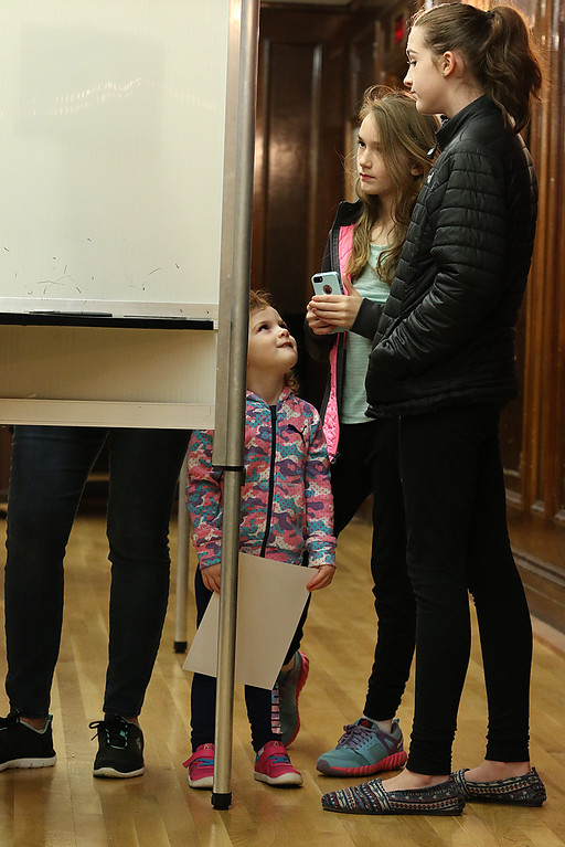 . Ameliah Breen, 2, with her sisters Savannah Breen, 12, and Kyleigh Breen, 10, watch as their mom Elizabeth Breen fills out her ballot at the polls at Leominster City Hall on Tuesday afternoon. SENTINEL & ENTERPRISE/JOHN LOVE