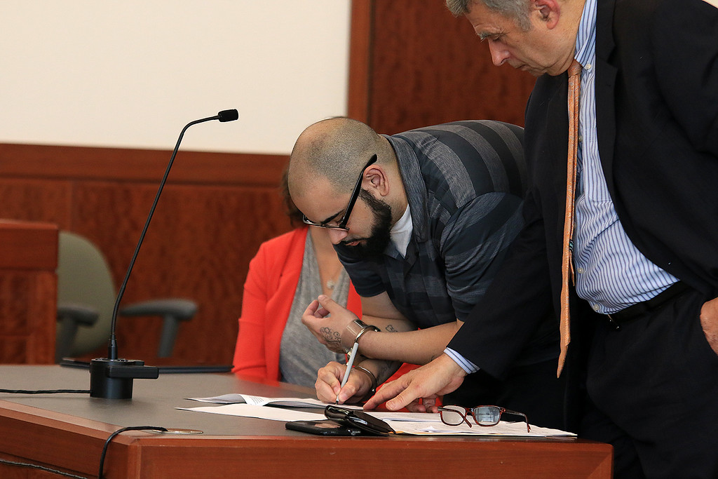 . Alberto Sierra was in Worcester District Court on Tuesday morning for a change of plea agreement to guilty. While in court he signed a document pertaining to his rights on the guilt plea while his lawyer Alan Black looks on. SENTINEL & ENTERPRISE/JOHN LOVE
