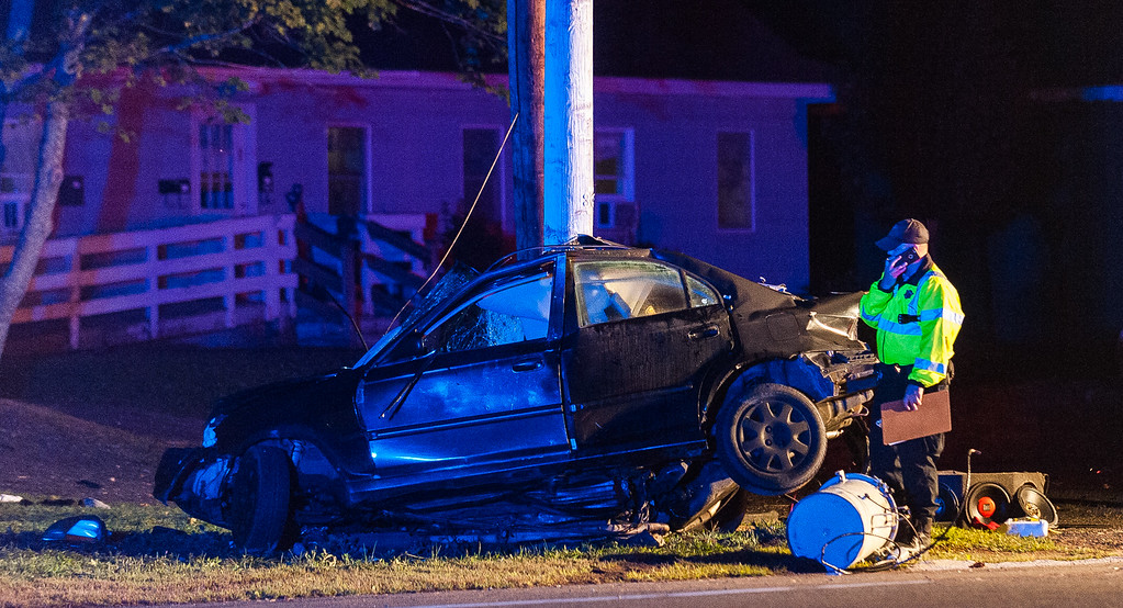 . A reconstructionist from the Mass State Police C.A.R.S. unit examines a car that slammed into a utility pole on East Broadway at Minott Rd in Gardner. SENTINEL&ENTERPRISE/ Jim Marabello