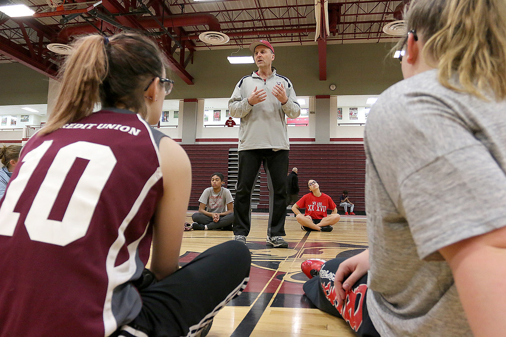 . New Fitchburg High School softball coach Mike Pelland talks to the team just before they started a throwing drills on Thursday afternoon in the gym at the high school. SENTINEL & ENTERPRISE/JOHN LOVE