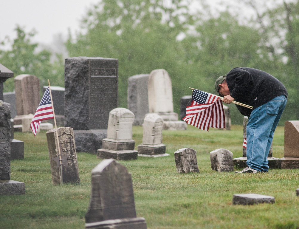 . Jim Galanis, a U.S. Army Veteran and volunteer from the American Legion Post 429, flags the graves of veterans at Forest Hill Cemetery in Fitchburg on Thursday, May 25, 2017 ahead of Memorial Day weekend. SENTINEL & ENTEPRISE / Ashley Green