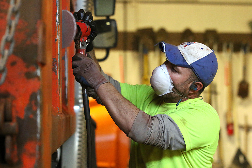 . Lunenburg Department of Public Works was getting ready for the 2017-18 winter season on Monday at their facility on Chase Road. DPW employee Chris Clark works on sanding down the side of one of the trucks to get it read for a new coat of paint on Monday. SENTINEL & ENTRPRISE/JOHN LOVE